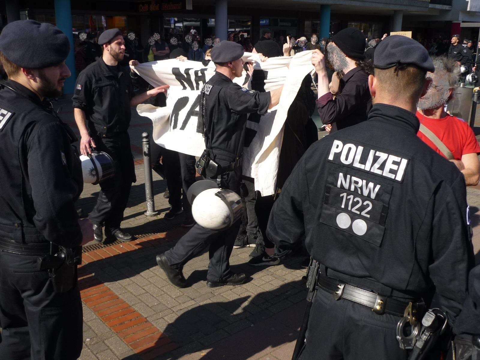 """Sanft werden die Gegendemonstranten in ihren """"Käfig"""" geschoben"""